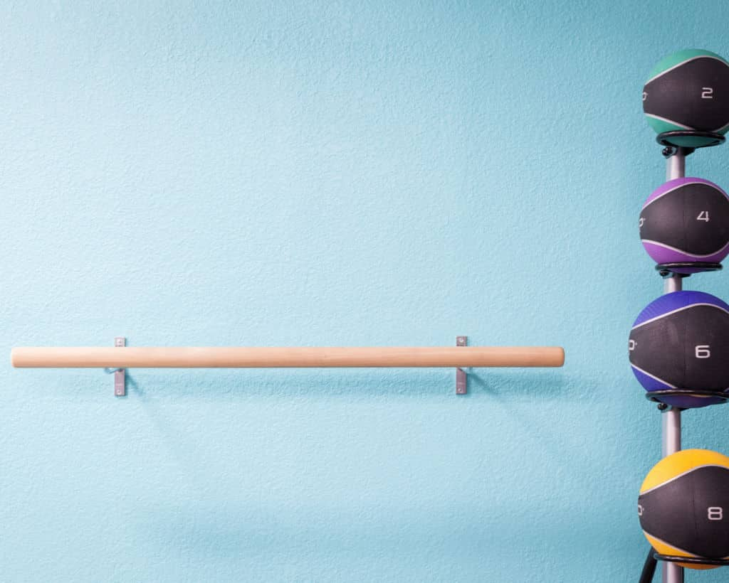 image of ballet bar with medicine balls in front of a bright blue wall