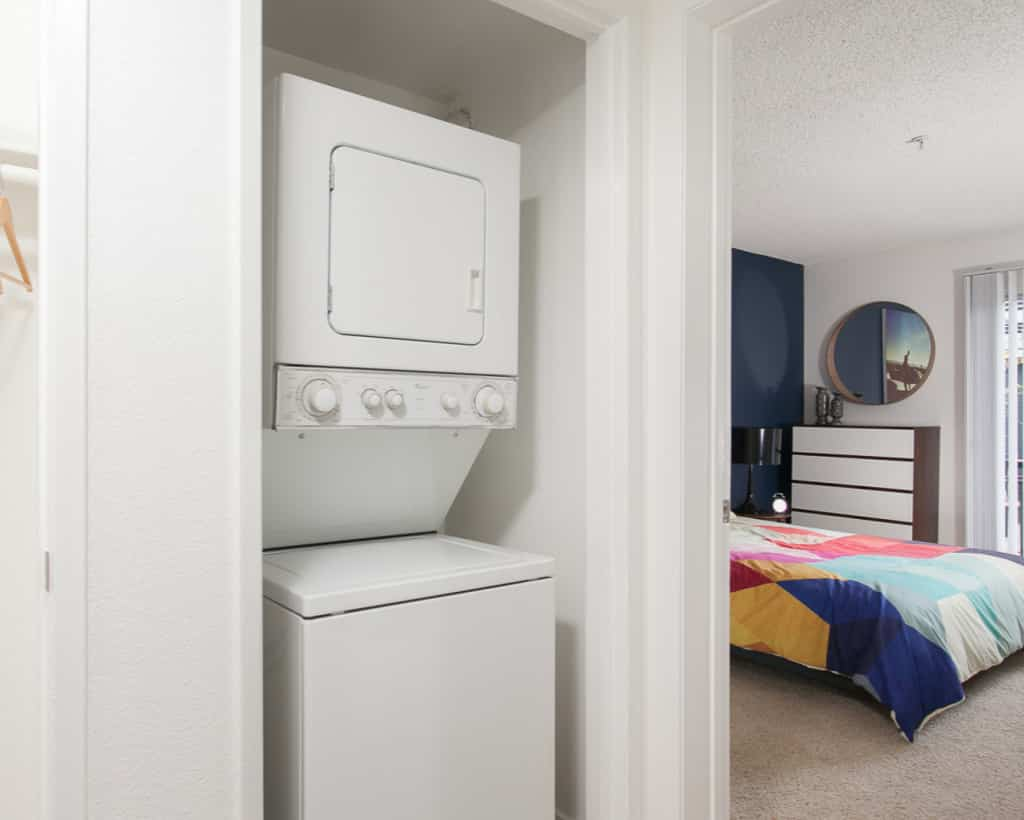 Stacked washer and dryer in the hallway with a closet to the left and the bedroom to the right