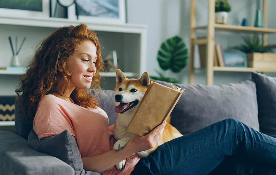 Woman sitting on a sofa while reading a book with dog