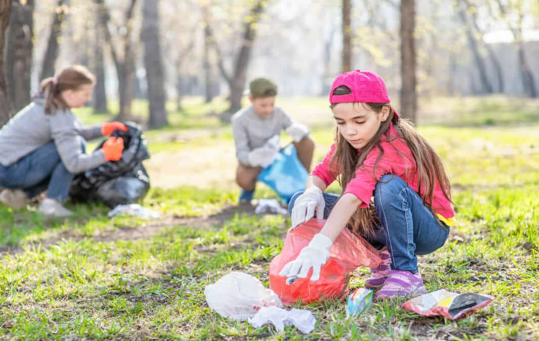 Teens picking up plastic garbage on the park